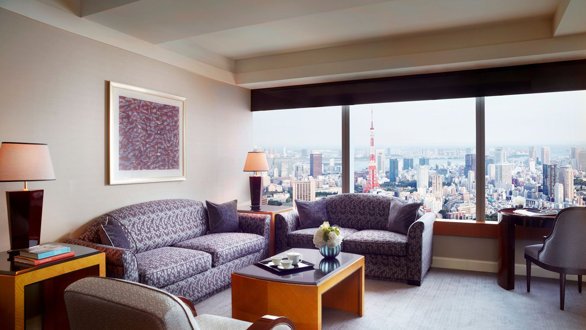 Suite living room with plush sofas, a wall of windows overlooking the city and a palette of grey, amethyst and white
