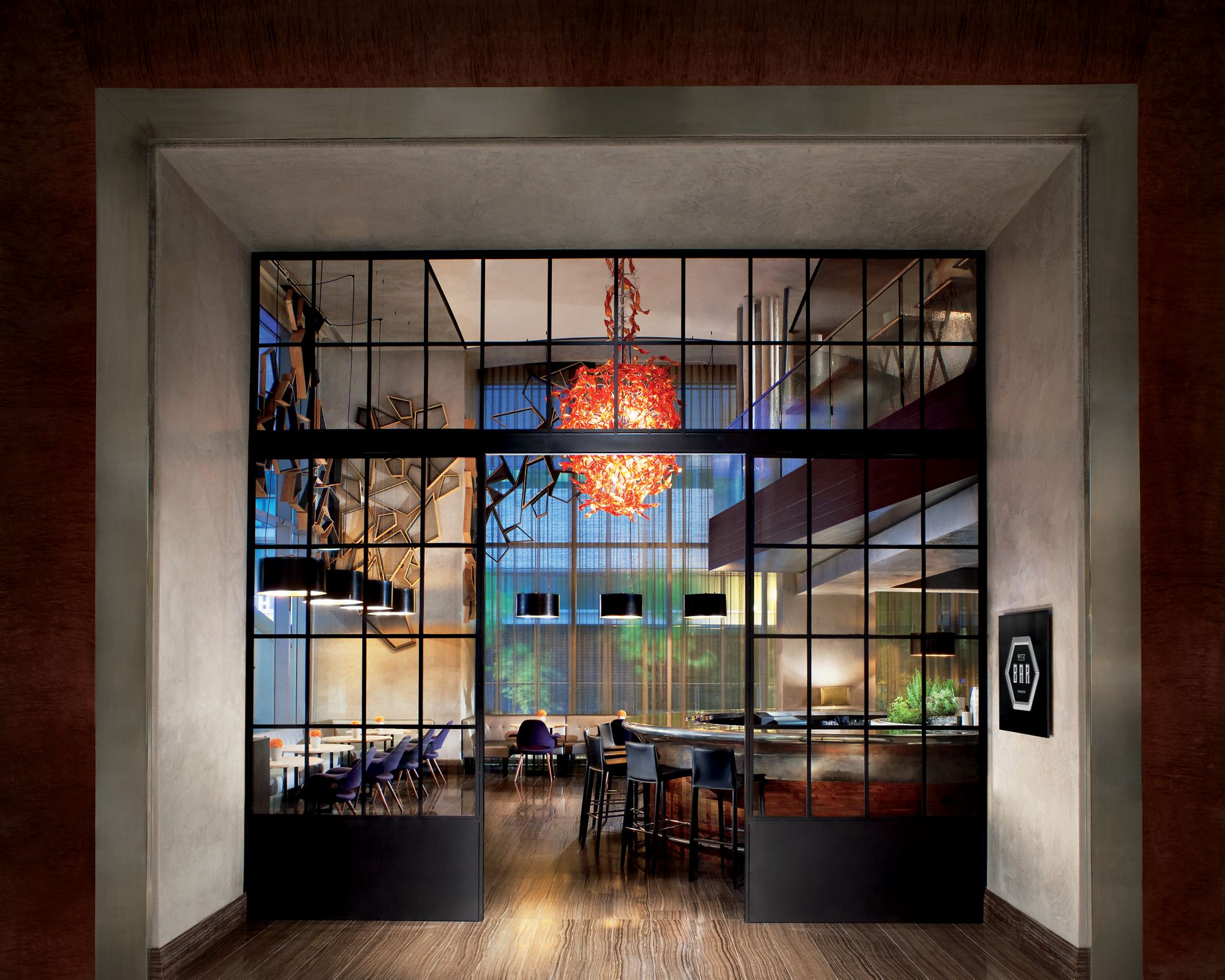 View through a glass wall of a two-level dining room with a bar and sculptural chandelier