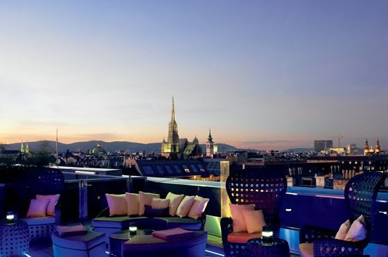 Rooftop bar with evening skyline views, lounge seating and colorful lights
