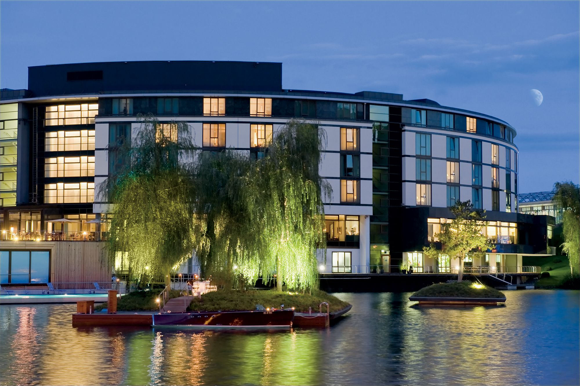 The Ritz-Carlton, Wolfsburg curves away from the lake into the evening sky