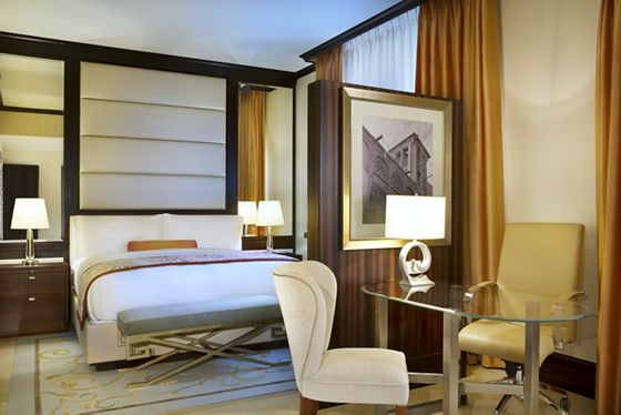 King bed and a glass desk in a bright and contemporary suite
