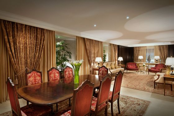 Vast dining room and living room with gold drapes, dark wood furniture and Persian rugs
