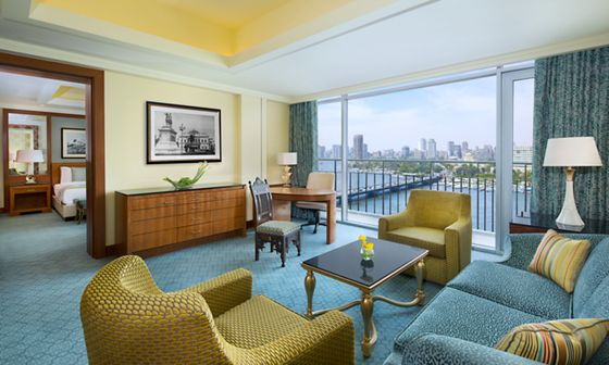 Light-infused living room of the Executive Suite featuring gold and wood accents, plush seating and expansive Nile views