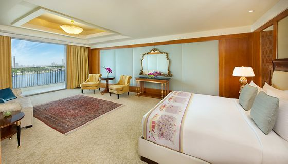 Large bedroom with pale cloth and wood wallcoverings, an area rug, a king-size bed and expansive Nile views