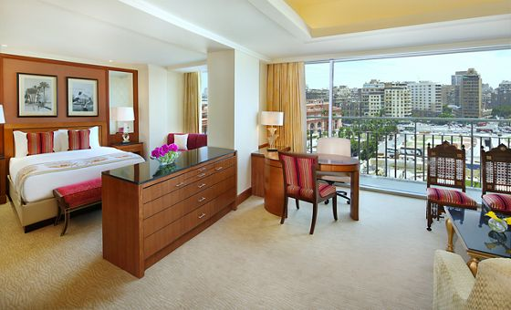 Suite with a partial wall and low cabinet dividing the bedroom and living room while expansive windows overlook the city