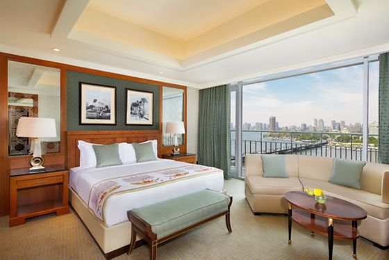 Suite bedroom done in sage, cream and wood with floor-to-ceiling windows that overlook the Nile