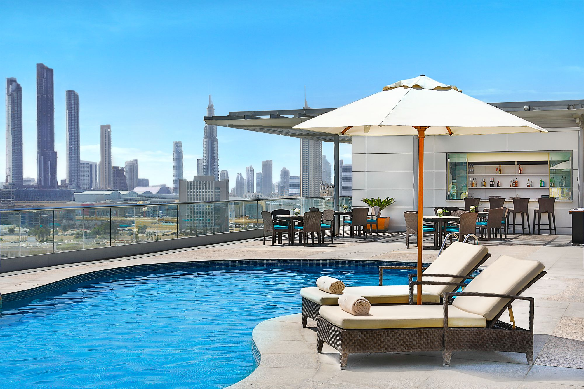 Outdoor pool overlooking the city skyline and flanked by outdoor seating, a bar and two chaise lounges