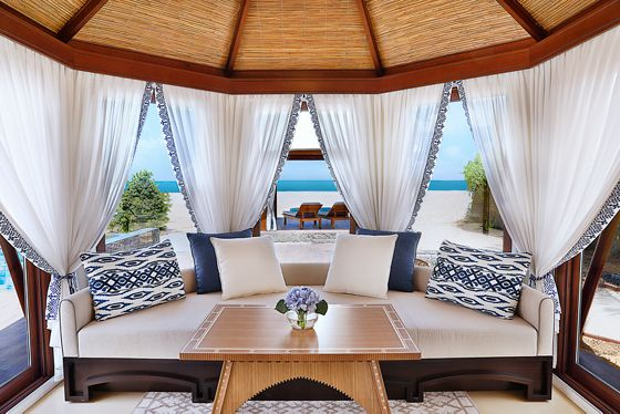 Villa sitting room with a tent-like, thatch roof and floor-to-ceiling windows with sheer drapes and ocean views