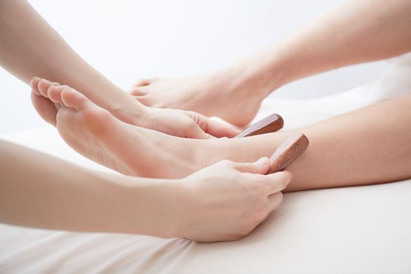 Spa therapist uses two small wooden instruments to massage a lady's ankle