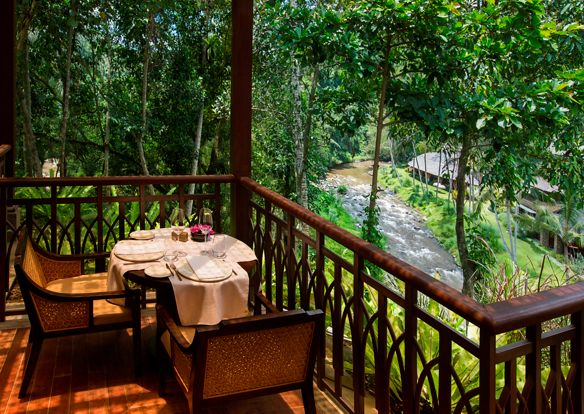 Table for two set on an outdoor terrace overlooking the Ayung River and rainforest