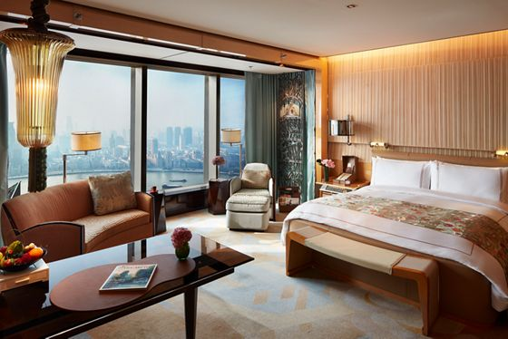 Guest room with a king-size bed, workspace and, near the floor-to-ceiling windows overlooking the river, plush seating