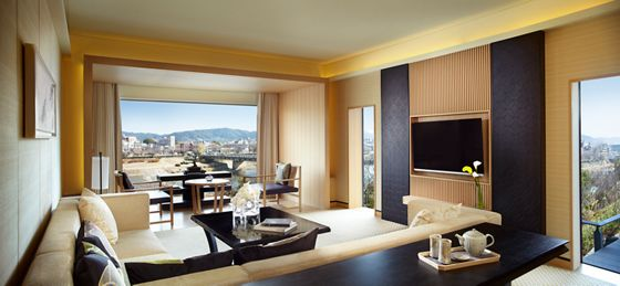 Room with sectional sofa, wall-mounted flat-screen TV and table in front of a floor-to-ceiling window overlooking the city