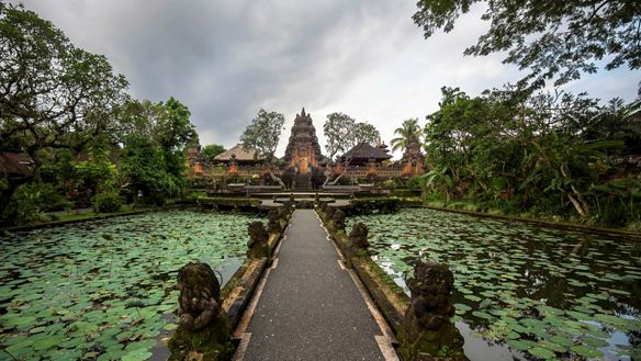 Long pathway flanked by water with lily pads leads to an orange temple under gray skies