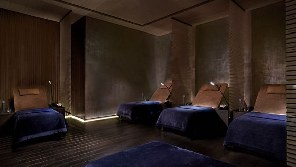 Dimly lit room with several lounge beds