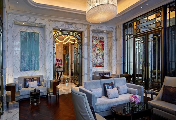 A room with marble walls, wood floors, sofas and large paintings