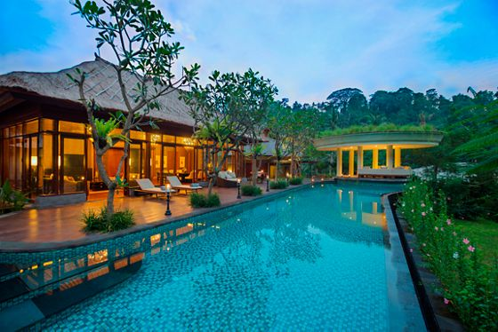 Long, sparkling pool next to a gently illuminated villa, all surrounded by rainforest as the sun sets