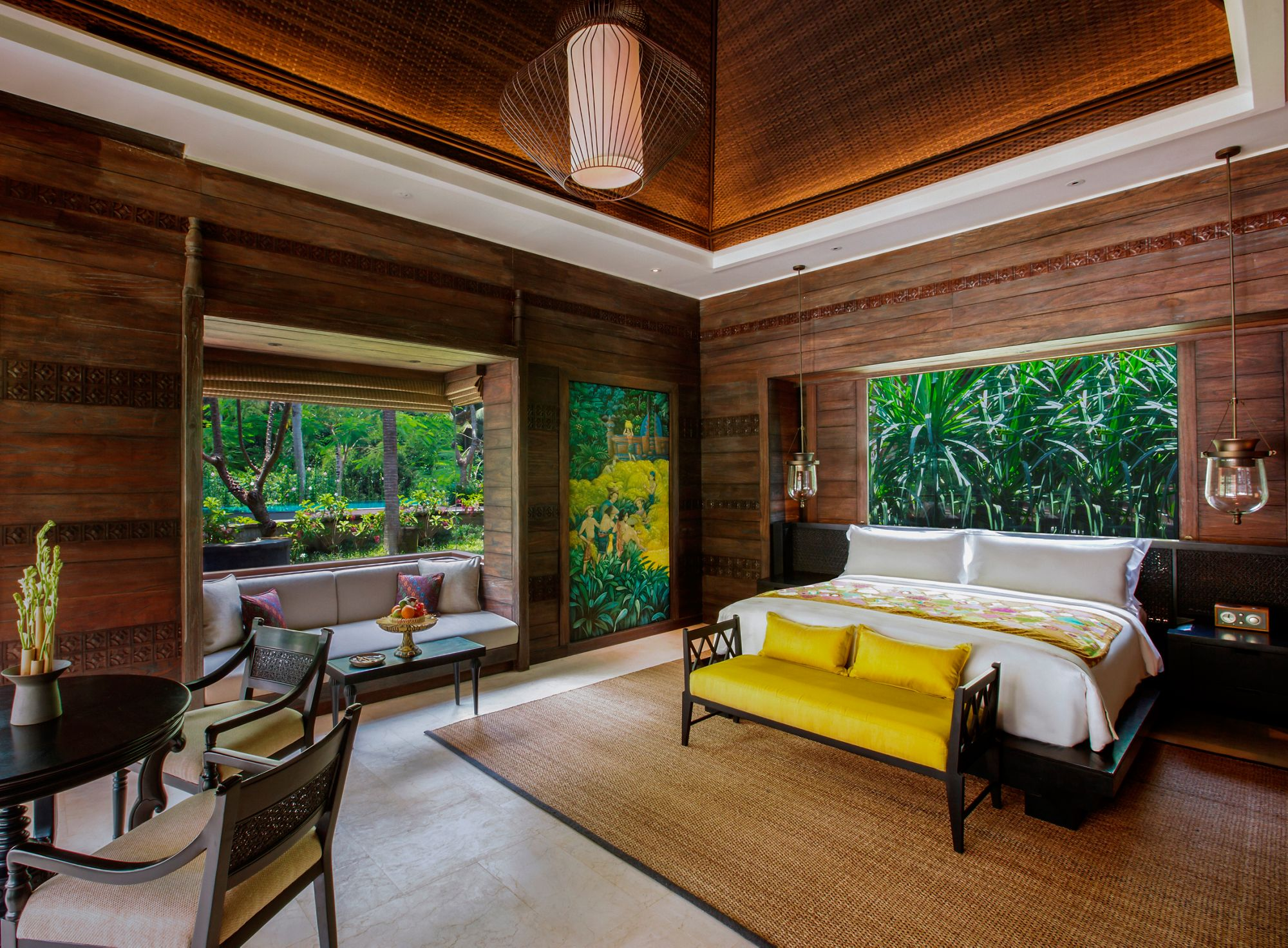 Villa bedroom with a king bed, window seat and a small table with chairs as well as wood-paneled walls and forest views