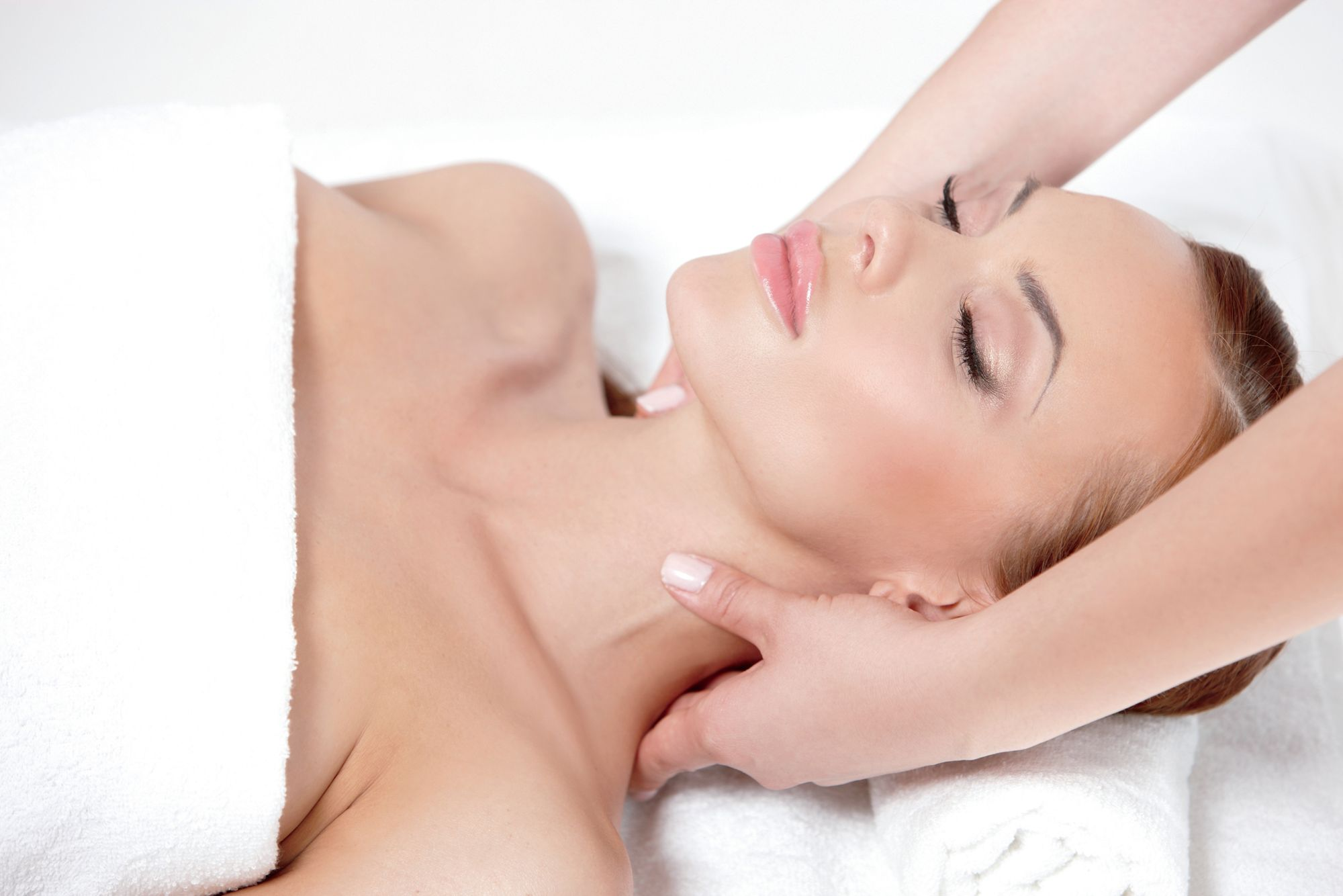 A woman lies on her back getting her neck massaged
