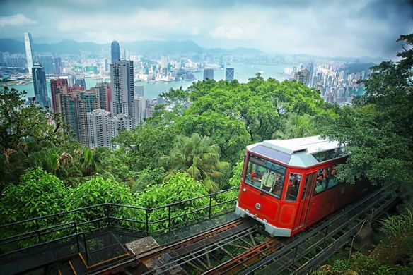 A tram climbs a track with a view of a large city