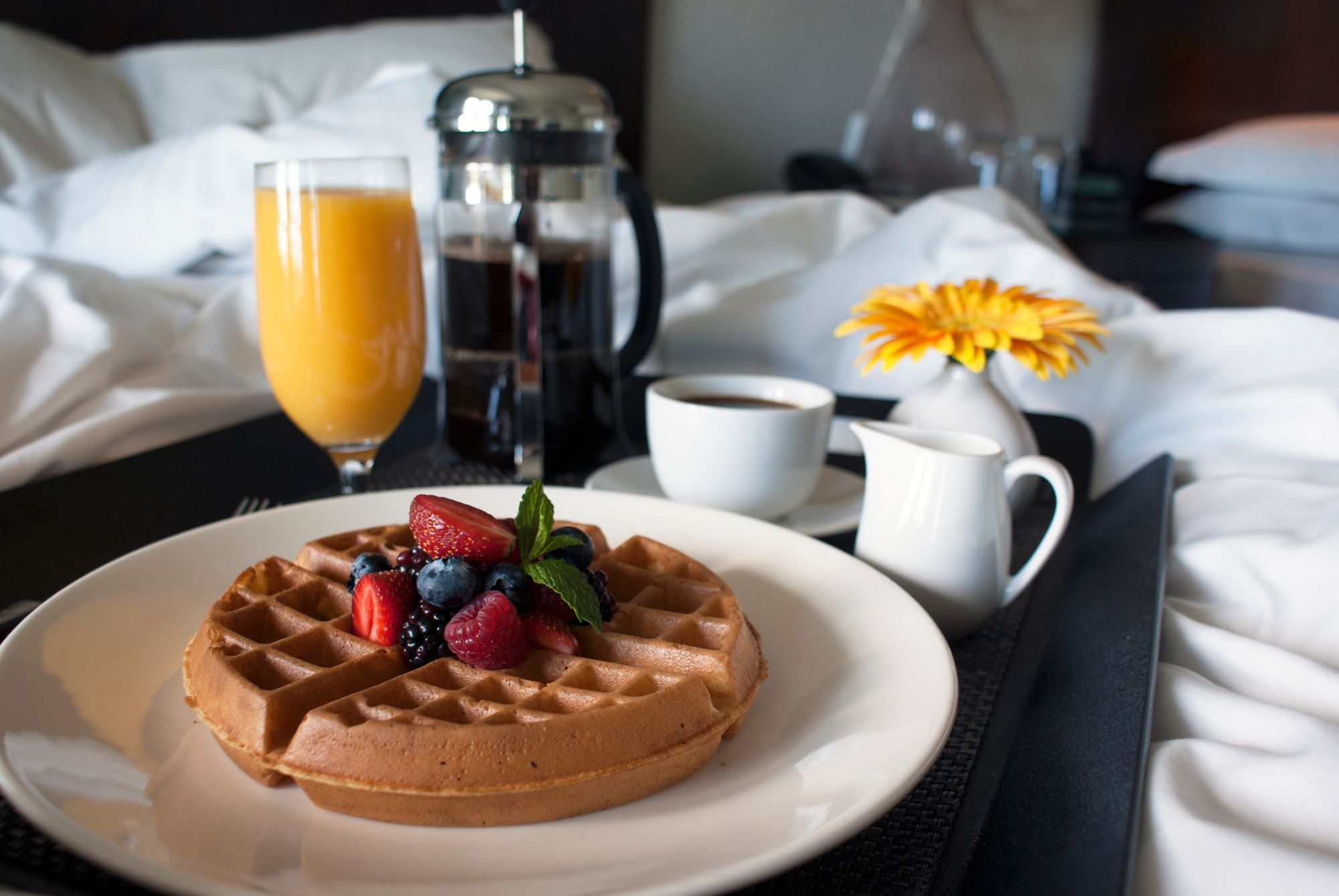 A waffle, coffee and juice on a tray