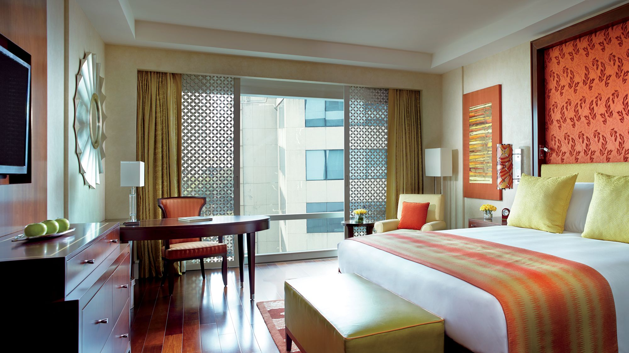 Guest room with floor-to-ceiling windows and city views, accents in red and yellow, a king-size bed and rich woods