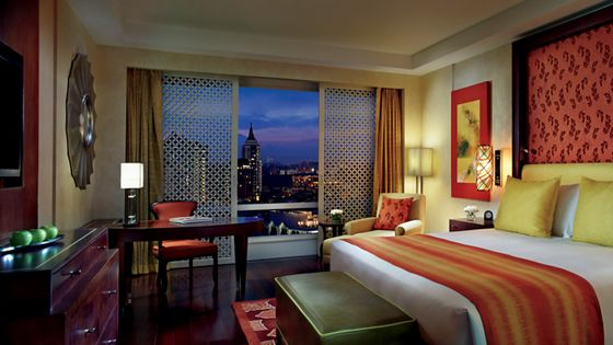 Guest room with evening city views from floor-to-ceiling windows, rich wood furniture and a king size bed in reds and yellows