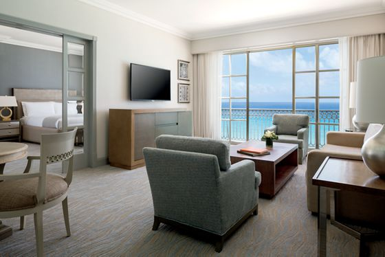 A living room leading to a balcony overlooking the ocean and a separate bedroom
