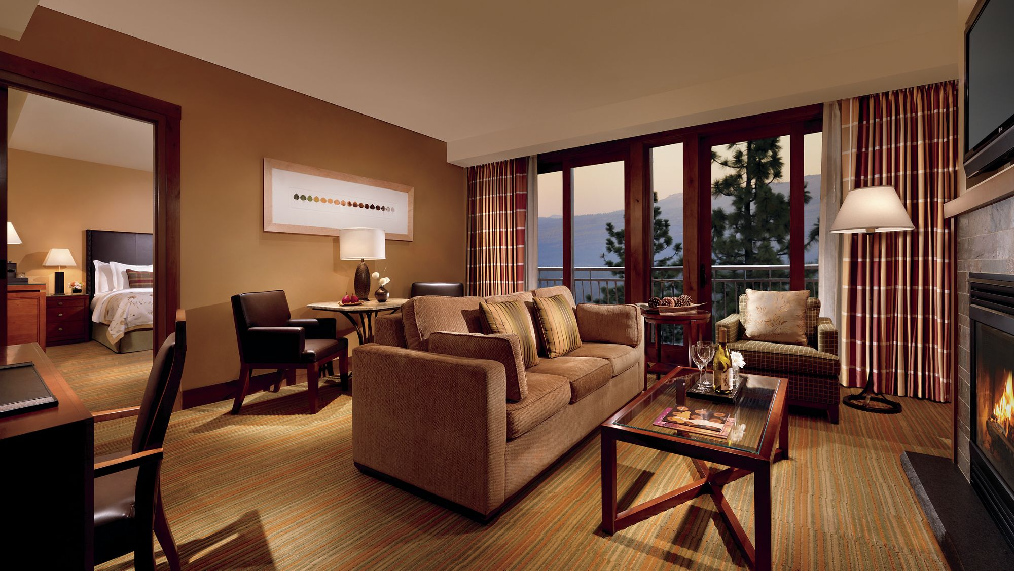 Suite living room with fireplace, flat-screen television and floor-to-ceiling windows