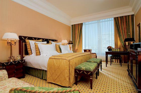 Guest room with green and gold décor, dark-wood furnishings, a king bed and two ottomans