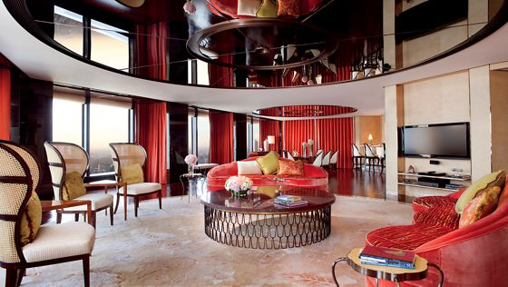 Vast living room with vaulted ceilings, floor-to-ceiling windows, red drapes and upholstery and accents in cream and espresso