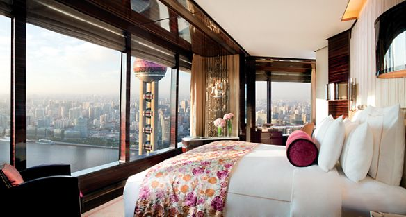 Bedroom where floor-to-ceiling windows wrap around the cornered walls to reveal views of the river and Pearl Tower