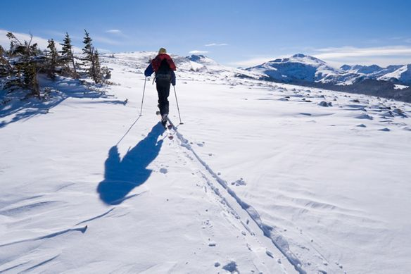 A man treks across the snow on skis