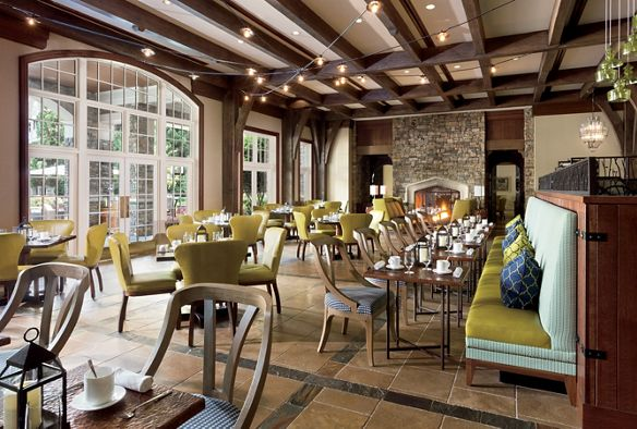 Wood-beamed room with stone fireplace and multiple dining tables and chairs