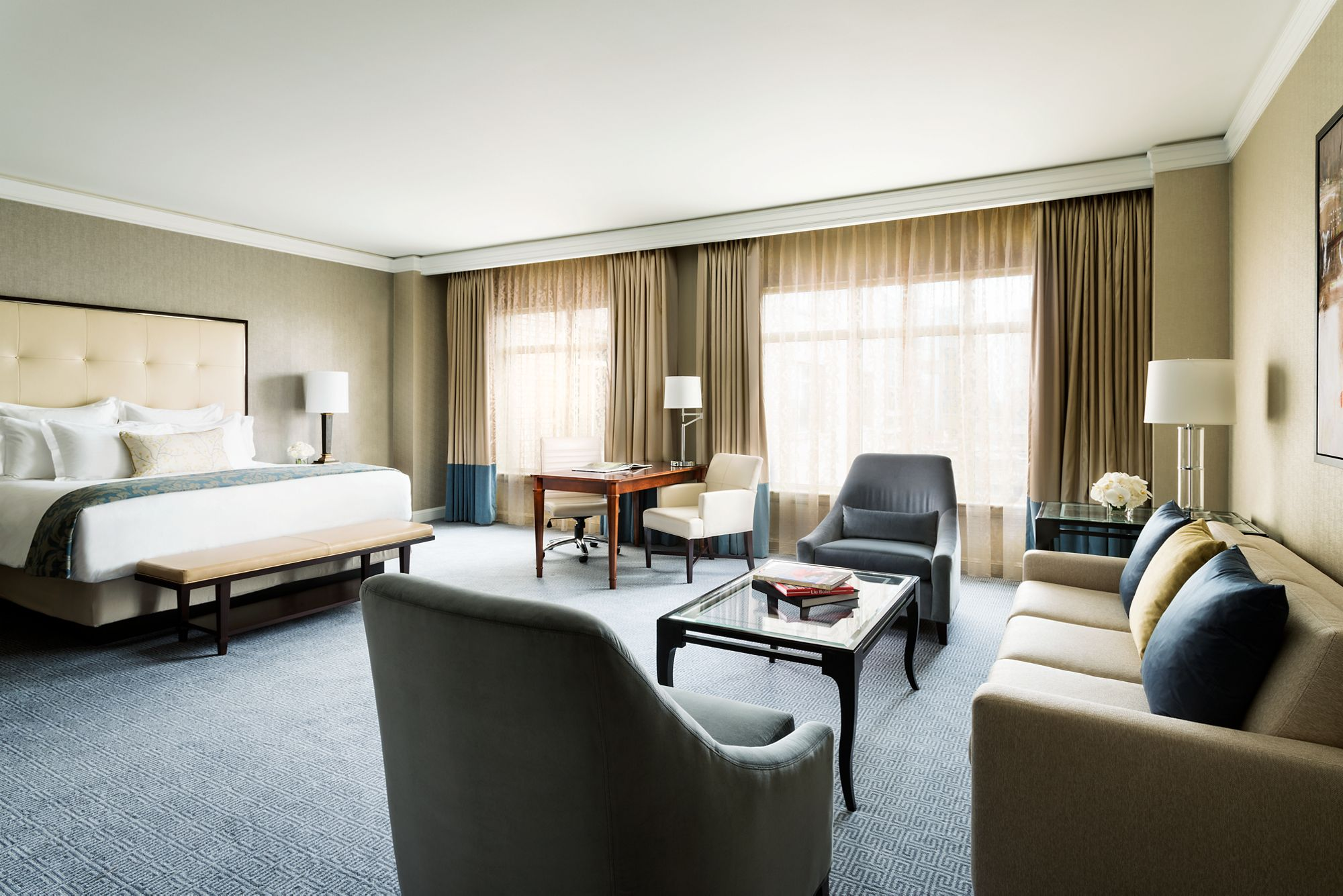 A large room with a king bed, spacious seating area, desk and two windows