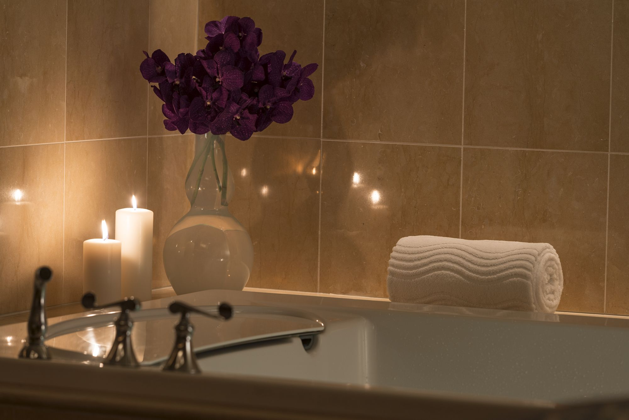 A tub with flowers and candles on the edge