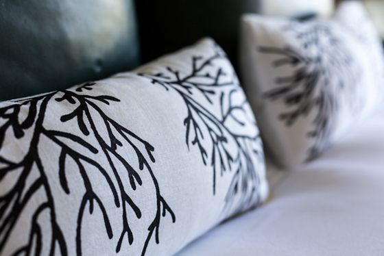 Close-up of bed pillows with a branch design