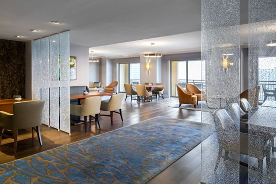 Open space with multiple dining tables and floor-to-ceiling windows overlooking the water