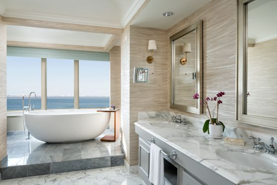 A marble bathroom with a standalone tub in front of a floor-to-ceiling window overlooking the ocean