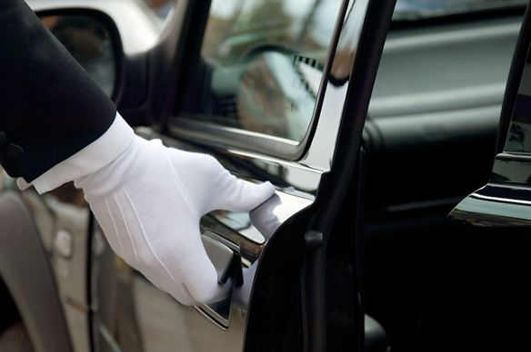 A gloved hand opens the door of a car