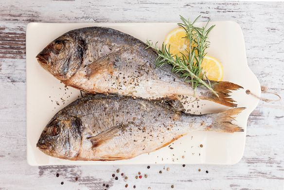 Two whole fish on a white cutting board with sprigs of rosemary and slices of lemon