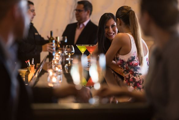 People gather around a bar talking and drinking cocktails