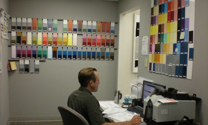Technician surrounded by color panels on wall