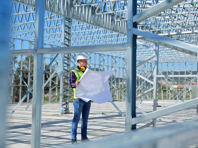 A contractor looking over blueprints inside of the steel frame of a building