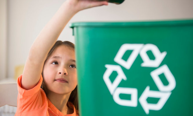 child recycling can into receptacle