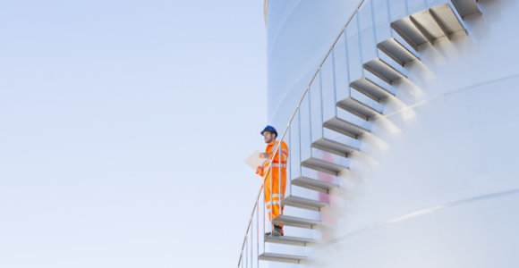 man standing on stairs attached to oil tank