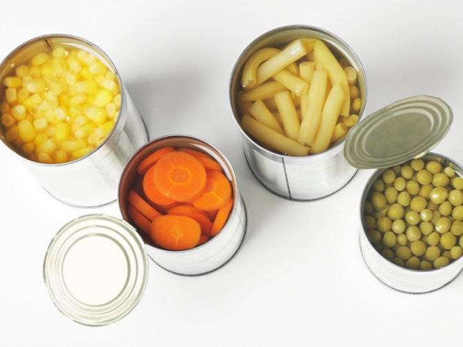Open food cans filled with beans, corn, carrots and peas