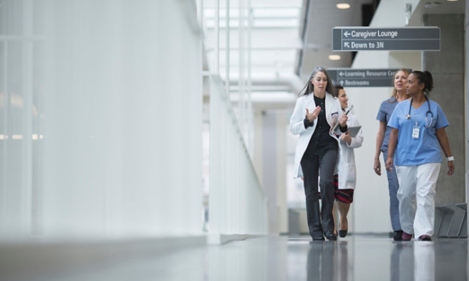 healthcare professionals walking in a hallway of health facility