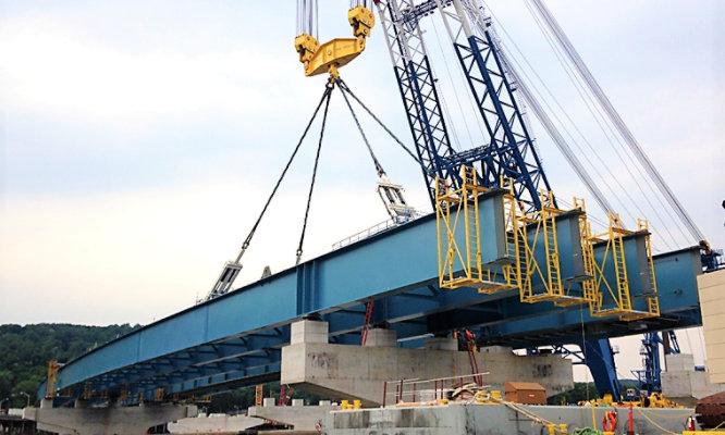 crane installing piece of bridge onto structure