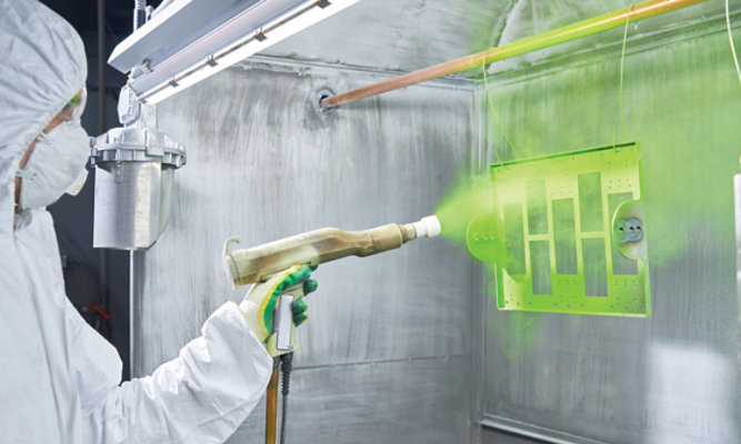 Technician spraying green powder on piece of equipment