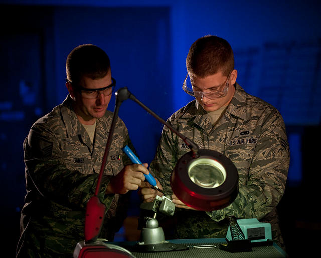 Airmen installing parts